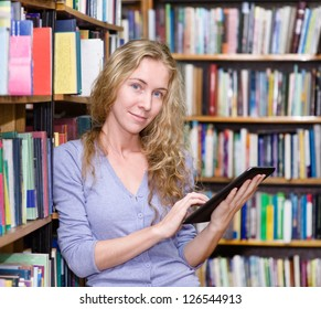 focused student using a tablet computer in a library. looking at camera