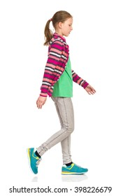 Focused teen girl in striped fleece jacket, jeans and sneakers walking and looking down. Side view. Full length studio shot isolated on white.