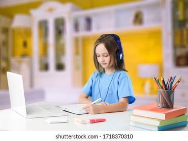 Focused teenage girl wearing headphones writing notes study and doing homework