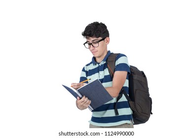 Focused teenager holding notebook writing with a smile, isolated on a white background.