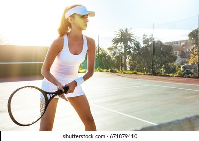 Focused tennis player ready for match on a sunny day. Sports woman playing on tennis court.