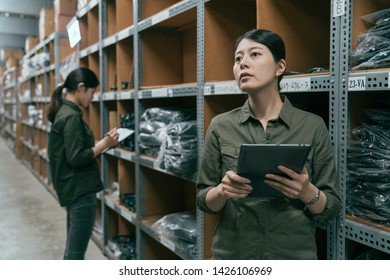 Focused warehouse manager woman using tablet checking stocks in large storehouse. young girl employee writing on clipboard in background. two female colleagues in uniform work in stockroom together