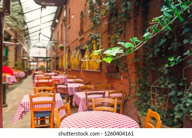Focused wild grape leaves on the background of Romantic summer outdoor cafe terrace with red cloth tables and wooden chairs. Horeca interior design concept. Selective focus, copy space