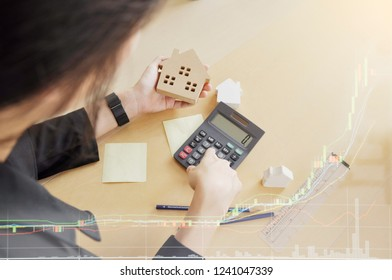 Focused woman hand on house mock up and  figuring out her finances ion the desk. Real estate agent handing over house mock up. Saving money for buy a new house or loan for plan business investment.