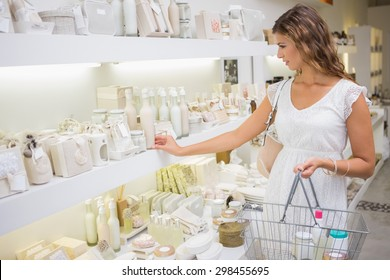Focused woman with shopping basket browsing products at a beauty salon