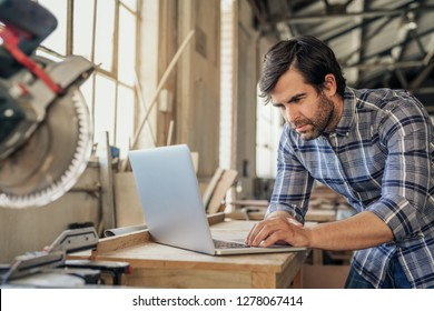 Focused woodworker leaning on a workbench by a mitre saw working online with a laptop in his woodworking studio