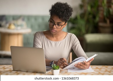 Focused young african american businesswoman or student looking at laptop holding book learning, serious black woman working or studying with computer doing research or preparing for exam online - Shutterstock ID 1361068373