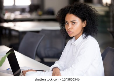 Focused young African American woman looking in distance at workplace, doubting female serious employee, student thinking of difficult job, question, task, received bad news, using laptop