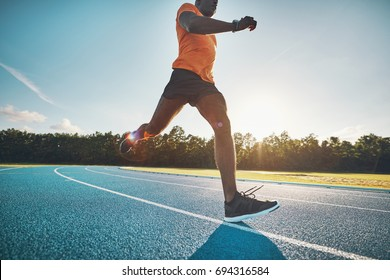 Focused young African male athlete in sportswear sprinting alone down a running track on a sunny day