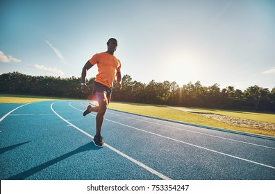 Focused young African male athlete in sportswear racing alone along a running track on a sunny day
