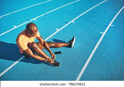 Focused young African male athlete sitting alone on a running track tying up his shoes before training