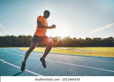 Focused young African male runner in sportswear sprinting alone along a running track on a sunny day