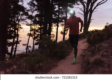 Focused young African man wearing a headlamp running alone down a trail in the forest while out for a cross country run at dusk
