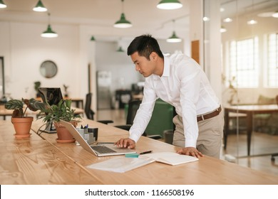 Focused young Asian businessman leaning on his desk in a modern office working online with a laptop and going over paperwork