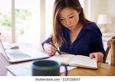 Focused young Asian businesswoman sitting at a table reading a notebook and using a laptop while working from home