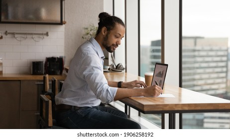 Focused young biracial man sales manager prepare summary report at home office check stats on pc screen make records on paper. Black male financial expert study stock prices rate growth graphs online