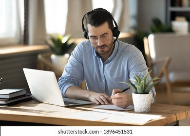 Focused young businessman in eyeglasses wearing wireless headset with microphone, involved in online video call negotiations meeting with partners colleagues or studying distantly, writing notes.