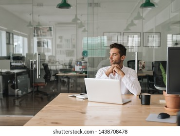 Focused young businessman looking deep in thought while working on a laptop at his desk in a modern office