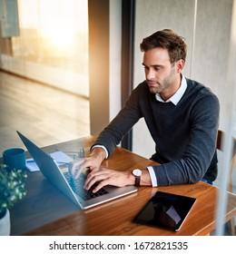 Konzentrierter junger Geschäftsmann, der am Esstisch in seiner Wohnung sitzt und online mit einem Laptop arbeitet