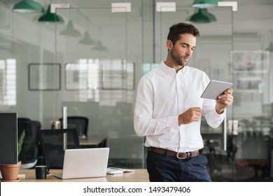 Focused young businessman standing alone in a large modern office working online with a digital tablet
