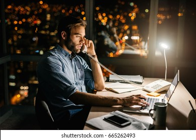 Focused young businessman talking on the phone while working overtime at his office desk late at night in front of windows overlooking the city