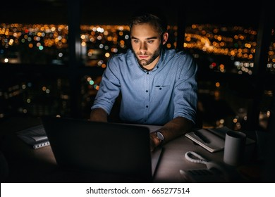 Focused young businessman working on a laptop at his office desk late in the evening in front of windows overlooking the city