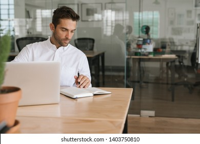Focused young businessman working online with a laptop and writing down notes while sitting alone at his desk in a modern office