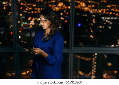 Focused young businesswoman using a digital tablet while standing alone in an office late at night in front of windows overlooking the city