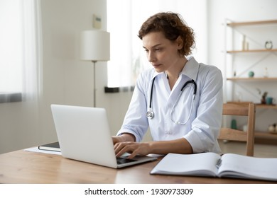 Focused young Caucasian woman doctor in white medical uniform sit at desk in hospital work on laptop online. Concentrated female nurse or GP look at computer screen consult patient on gadget.