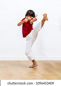 focused young child showing dynamic grace and positive energy with fighting legs and fingers for kid's martial art and motivation over wooden floor, white background