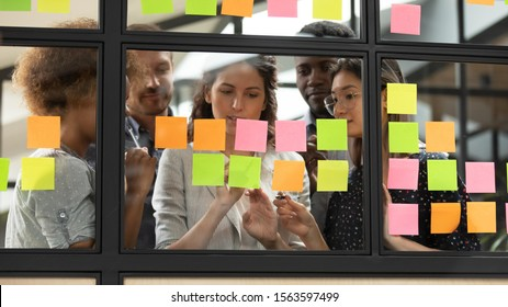 Focused young diverse teammates working with caucasian team leader on IT startup project kanban organization process, discussing details and tasks, writing notes on colorful paper stickers at office.