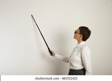 Focused young female teacher in conservative clothing teaching a lesson at a whiteboard holding a black plastic pointer