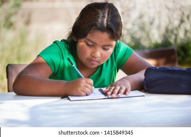 Focused young girl writting in her notebook, problem solving and studying outdoors in homeschool setting.