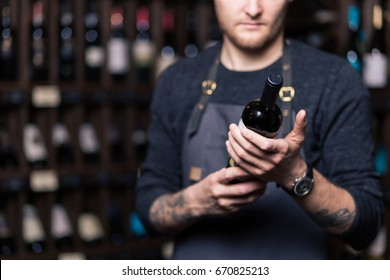 Focused young male sommelier in suite looking at red wine in bottle