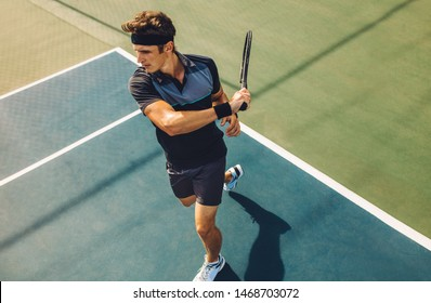 Focused young male tennis player hitting a forehand. Tennis player playing a match on hard court.