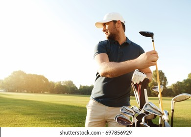 Focused young man golfer taking out the golf club from a bag while standing on a field