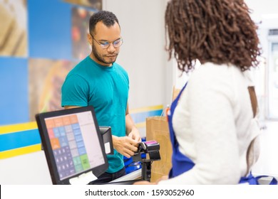 Focused young man paying bill in store. Back view of cashier standing at workplace. Shopping concept