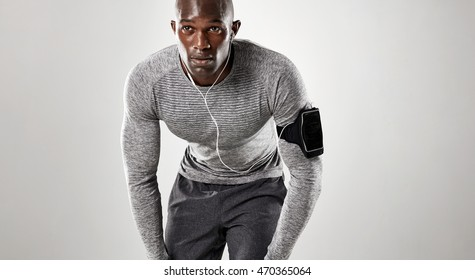 Focused young man ready for running over grey background. Muscular african male model in sportswear.