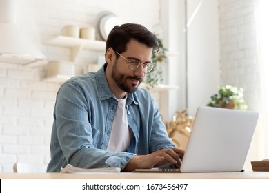 Focused young man wearing glasses using laptop, typing on keyboard, writing email or message, chatting, shopping, successful freelancer working online on computer, sitting in modern kitchen - Shutterstock ID 1673456497