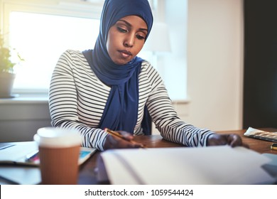Focused young Muslim female entrepreneur wearing a hijab reading through paperwork while working at table in her home office