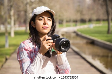 Focused young photojournalist working outdoors. Young woman wearing cap holding photo camera at face and looking away. Occupation concept