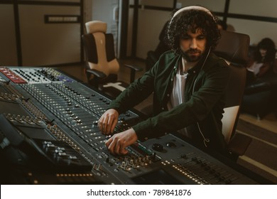 focused young sound producer working at studio