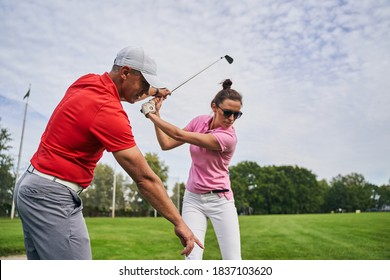 Focused young woman golfer holding a mid-iron over her head helped by her personal trainer