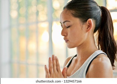 Focused young woman meditating while practicing yoga.