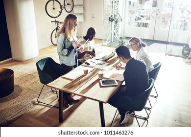 Focused young woman talking to a group of colleagues sitting together around a table in a modern office