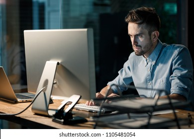 Focusing man sitting at table in office using computer having overhours and doing project work.