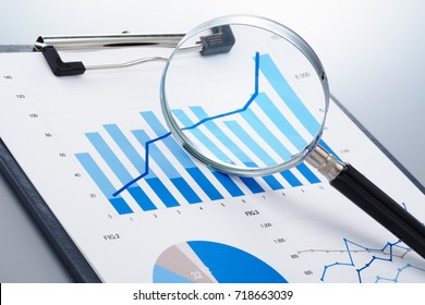Focusing on growth potential. Reviewing report. Magnifying growth chart. Document and magnifying glass on reflection background.