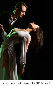 Focusing on the love affair. Couple of mime artists perform romance on stage. Theatre actors miming through body motions. Mime man and woman act in romantic scene. Couple in love with mime makeup.