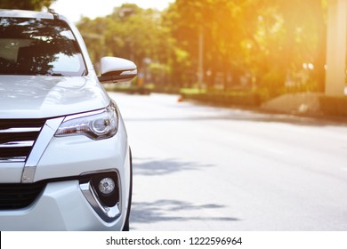 Focusing on the White car headlights on a street corner with sunlight flares, In the background, the driver, bike and car. Car parking on the street.