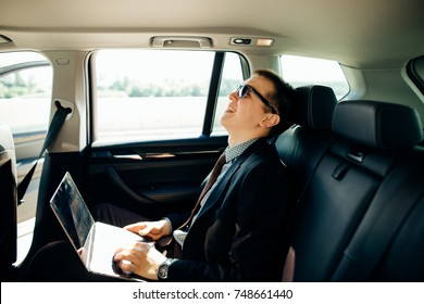 Focusing on work. Handsome young businessman working on his laptop and talking on the phone while sitting on the back seat of the car